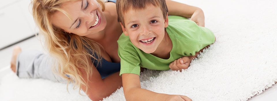 Mom and a boy playing on carpet