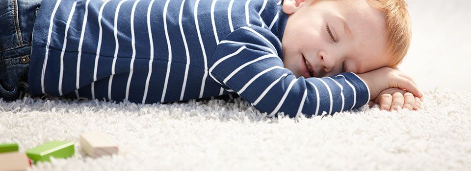 Boy sleeping on carpet